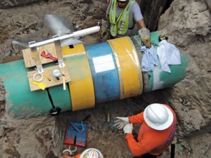 "APPLICATION IN LIMITED CLEARANCE EXCAVATION Here, a spool feeder operates in a ""bell-hole,"" showing how this simple tool eases installation in limited excavation areas."